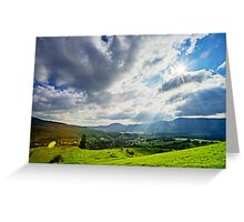 Sun shining through the clouds over beautiful green valley Greeting Card