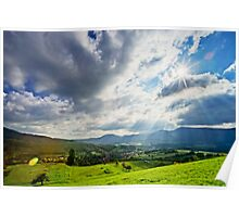 Sun shining through the clouds over beautiful green valley Poster