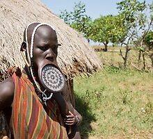 Woman of the Mursi tribe with clay lip disc as body ornaments by PhotoStock-Isra