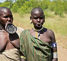 two women of the Mursi tribe with clay lip disc as body ornaments  by PhotoStock-Isra