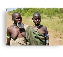 two women of the Mursi tribe with clay lip disc as body ornaments  Canvas Print