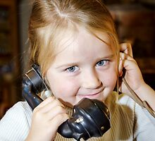 Cute preschooler girl talking by old vintage retro telephon, closeup portrait by Alexander Sorokopud