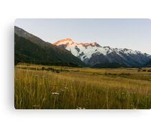 Mount Cook National Park at daybreak as rising sun strikes peaks of surrounding mountains Canvas Print