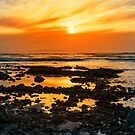 deep orange reflections at rocky beal beach by morrbyte