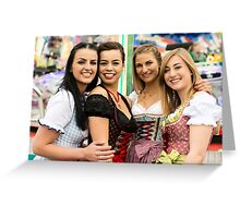 Joyful young and attractive women at German funfair Oktoberfest with traditional dirndl dresses and joyride in the background. Greeting Card