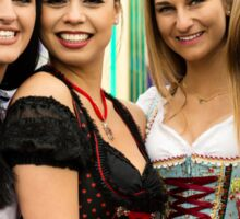 Joyful young and attractive women at German funfair Oktoberfest with traditional dirndl dresses and joyride in the background. Sticker