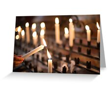 Woman lighting prayer candle aka offering, sacrificial or memorial candles lit in a church Greeting Card