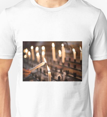 Woman lighting prayer candle aka offering, sacrificial or memorial candles lit in a church Unisex T-Shirt