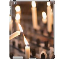 Woman lighting prayer candle aka offering, sacrificial or memorial candles lit in a church iPad Case/Skin