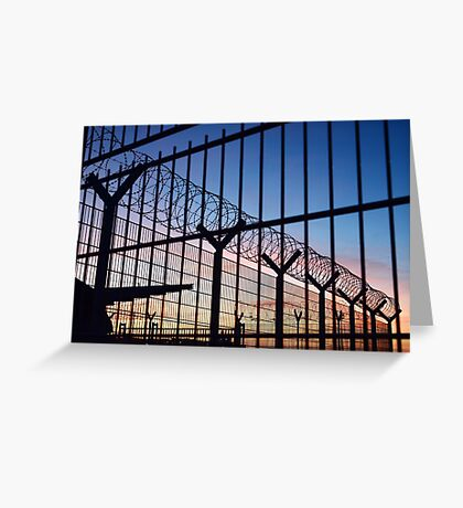 View through a barbed wire fence with beautiful colourful sunset sky in Dieppe France Greeting Card