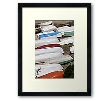 pile rowing boats on the shore Framed Print