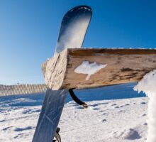 Snowboard leaning on a wood rail Sticker