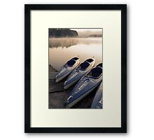 Kayak canoe boats at lake shore in morning fog Framed Print