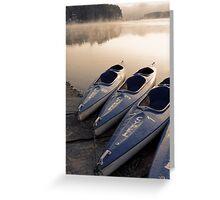 Kayak canoe boats at lake shore in morning fog Greeting Card