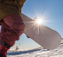 Snowboarder walking against blue sky Sticker