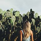 Young Blond Girl Standing in Front on Cacti by visualspectrum
