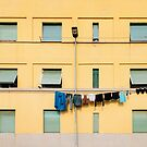 Laundry Drying on Washing Line Against Yellow Building Facade in Italy by visualspectrum