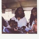 Polaroid of Young Hippie Family of Three Singing Inside Camper Van by visualspectrum
