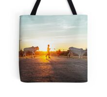 Silhouette of Boy Leading Cattle Across Road at Sunset in Burmese Countryside Tote Bag