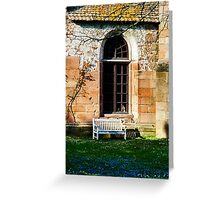 Lonely bench under the wall of old church. Spring lawn with blue florets. Greeting Card