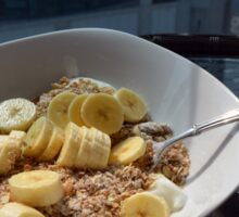 A bowl of cereals with yogurt and bananas. Sticker