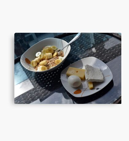 A bowl of cereals and yogurt and a plate with cheese and eggs. Canvas Print