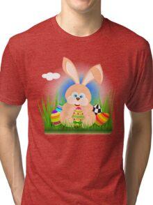 Cartoon easter rabbit on grass holding an easter egg Tri-blend T-Shirt