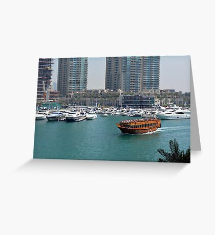 Photography of tall buildings, skyscrapers from Dubai and wooden boat crossing the water. United Arab Emirates. Greeting Card