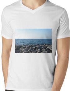 The sea and blue sky, and rocks at the shore. Mens V-Neck T-Shirt
