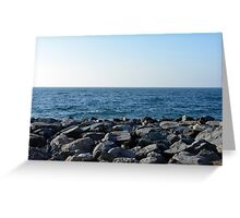 The sea and blue sky, and rocks at the shore. Greeting Card