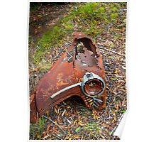 Rusted car fender laying in junk yard Poster