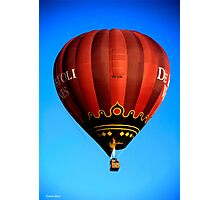 Red hot air balloon in flght on blue sky. Photographic Print