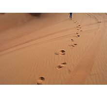 Man walking in the desert leaving footsteps in the sand. Photographic Print