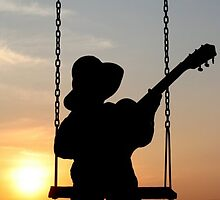 Toddler playng guitar during sunset - Silhouette by Qnita