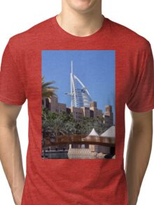 Photography of Arabic buildings and wooden bridge in front of Burj al Arab hotel from Dubai, United Arab Emirates. Tri-blend T-Shirt