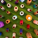 Multicolor sewing threads on wooden background by Bruno Beach