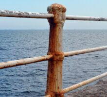 The sea and promenade with rusty white handrail. Sticker