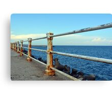 The sea and promenade with rusty white handrail. Canvas Print