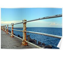 The sea and promenade with rusty white handrail. Poster