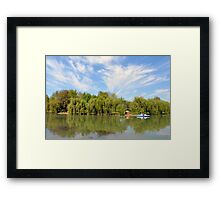 Park scenery with dramatic sky and trees by the river. Framed Print