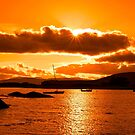 boats in a quiet bay at sunset by morrbyte
