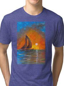 A boat sailing against a vivid colorful sunset  Tri-blend T-Shirt