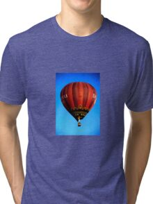 Red hot air balloon in flght on blue sky. Tri-blend T-Shirt