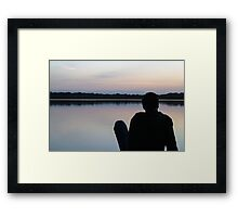 Man on the pier watching the sunset Framed Print