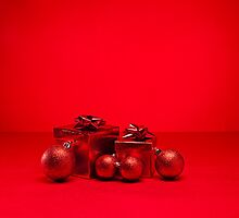 Red bauble and present in red Christmas setting by 3523studio