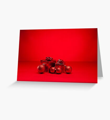 Red bauble and present in red Christmas setting Greeting Card