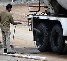 man washing concrete mixer truck by bayu harsa