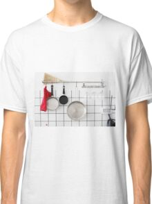 Frying pans hang on a wall of a domestic kitchen  Classic T-Shirt