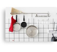Frying pans hang on a wall of a domestic kitchen  Canvas Print