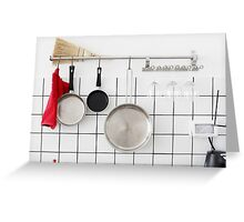 Frying pans hang on a wall of a domestic kitchen  Greeting Card